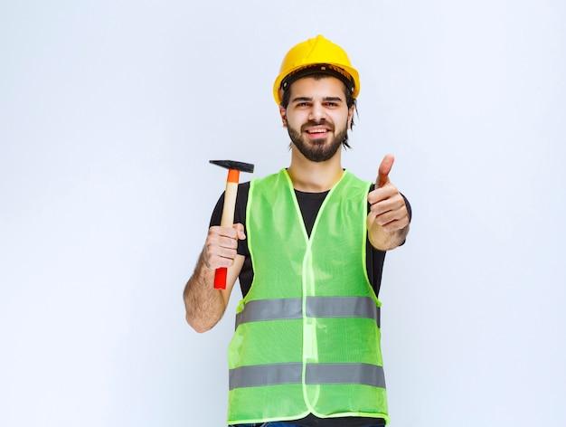 Pracownik budowlany, trzymając młotek pazur i pokazując znak przyjemności.