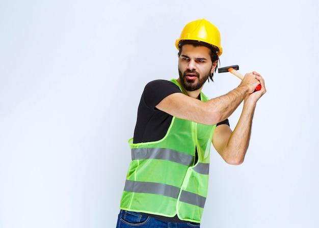 Pracownik budowlany, trzymając młotek pazur i uderzając w gwóźdź.