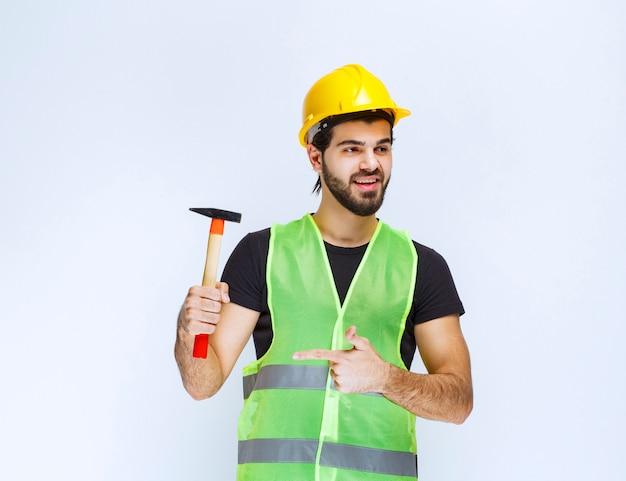 Pracownik budowlany, trzymając młotek pazur.