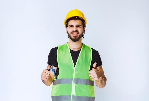 Pracownik budowlany, trzymając niebieski szczypce i pokazując kciuk do góry.
