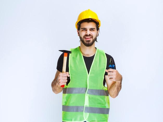Pracownik budowlany, trzymając w ręku niebieski szczypce i młotek pazurowy.