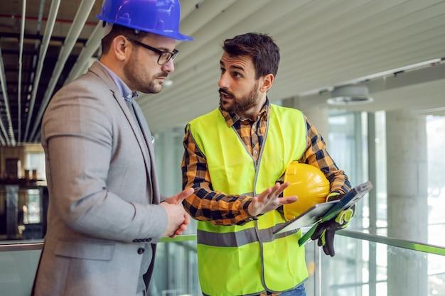 Pracownik budowlany trzymający tablet i wyjaśniający przełożonemu, jak idą prace. budynek w trakcie budowy wnętrza.