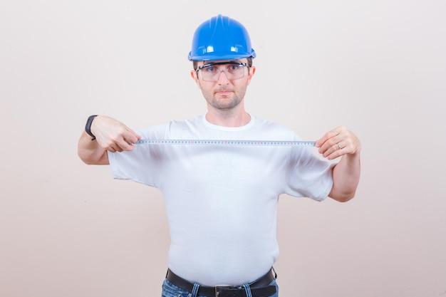 Pracownik budowlany trzymający taśmę pomiarową w koszulce, dżinsach, kasku i wyglądającym pewnie