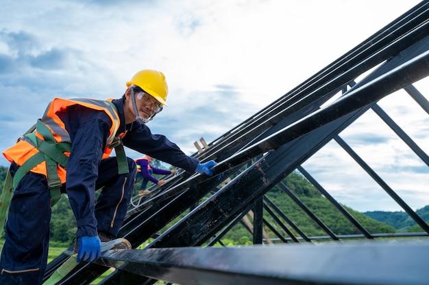 Pracownik budowlany ubrany w szelki bezpieczeństwa i linę bezpieczeństwa pracujący na wysokim miejscu na placu budowy.