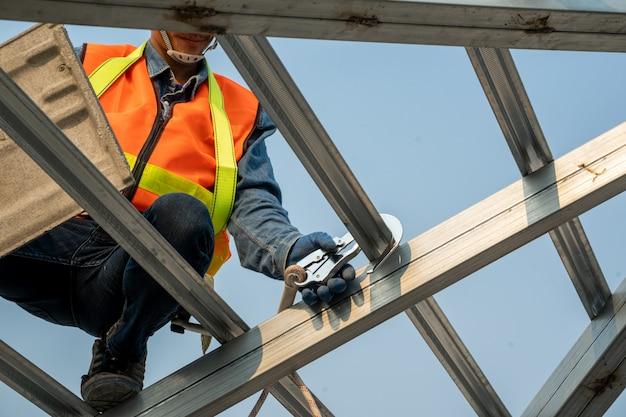Pracownik budowlany ubrany w uprząż bezpieczeństwa i linę bezpieczeństwa pracujący na wysokim miejscu instaluje nowy dach, konstrukcja dachu z dachówkami.