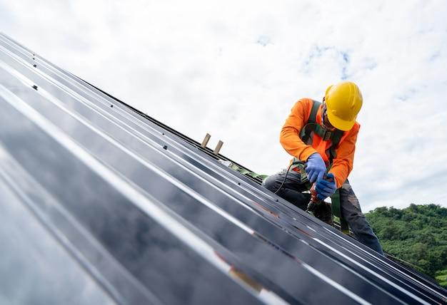 Pracownik budowlany ubrany w uprząż bezpieczeństwa i linię bezpieczeństwa pracujący na wysokich dachach instaluje nowy dach.