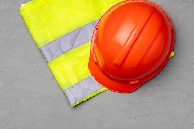 Pracownik budowlany ustawił kask i widok z góry kamizelki fluorescencyjnej