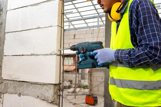 Pracownik budowlany używa wiertła, inżynier noszący wyposażenie ochronne (hełm i płaszcz) używa wiertarki do zamontowania napowietrzonej ściany z cegły.