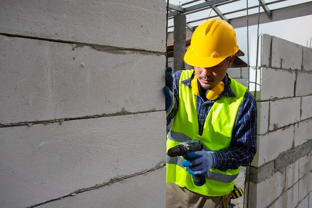 Pracownik budowlany używa wiertła, inżynier w hełmie i kurtce bezpieczeństwa używa wiertarki do zamontowania napowietrzonej ściany z cegły.