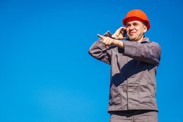Pracownik budowlany w hełmie przeciw niebieskiemu niebu opowiada na telefonie.