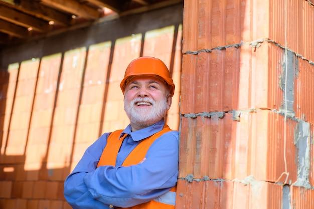 Pracownik budowlany w koncepcji konstruktora przemysłu naprawy kasków brodaty mężczyzna w garniturze z budową
