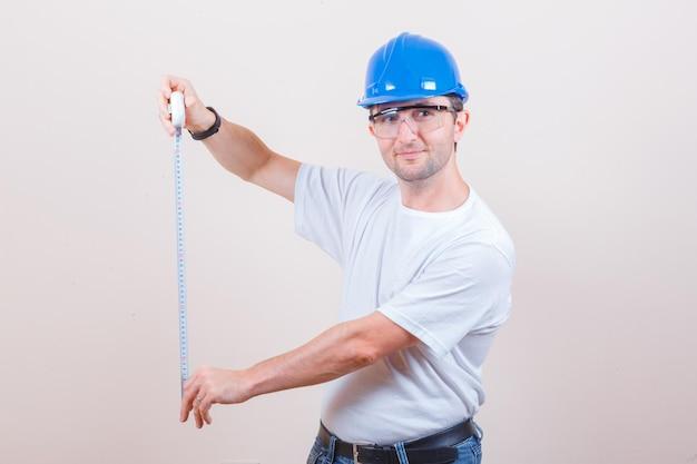 Pracownik budowlany w koszulce, dżinsach, kasku trzymającym taśmę pomiarową i wyglądającym wesoło