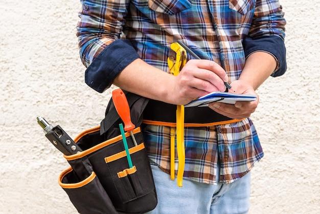 Pracownik budowlany w niebieskiej koszuli w kratkę z narzędziami w pasku robi notatkę ołówkiem w zeszycie.