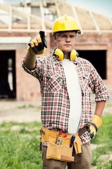 Pracownik budowlany, wskazując na coś