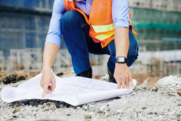 Pracownik budowlany wskazujący na plan budynku