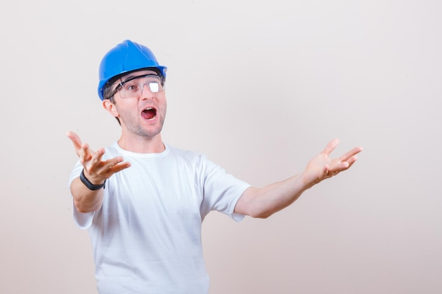 Pracownik budowlany wyciąga ręce w koszulce, kasku i wygląda na zaskoczonego