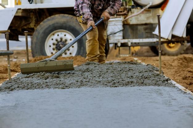 Pracownik budowlany wylać cement na chodnik w betonowych pracach betonomieszarką z taczką
