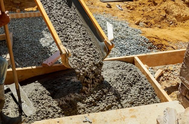 Pracownik budowlany wylać cement na chodnik w betonowych pracach z betonomieszarką z taczką
