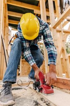 Pracownik budowlany z ciężkim kapeluszem szlifowanie kawałka drewna