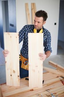 Pracownik budowlany z drewnianymi deskami