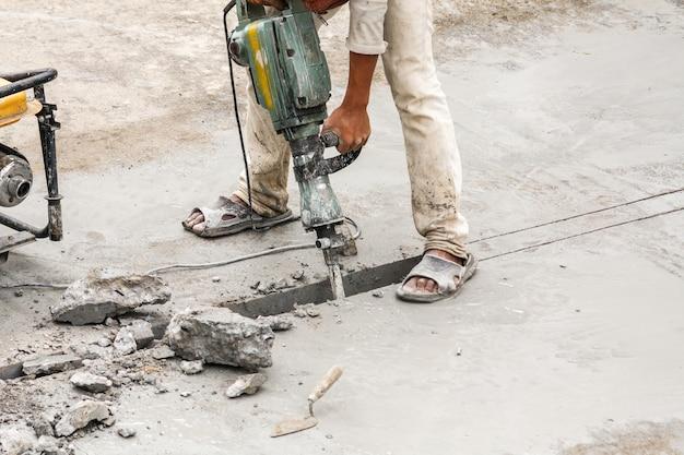Pracownik budowlany za pomocą młota pneumatycznego wiercenia powierzchni betonu
