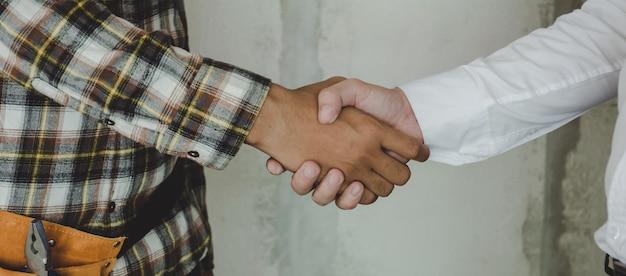 Pracownik budowlany zespół wykonawca drżenie ręki z inżynierem po zakończeniu spotkania biznesowego w celu rozpoczęcia umowy projektu w budynku budowy