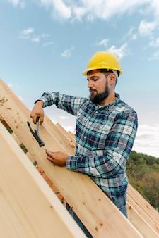 Pracownik budujący dach domu