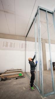 Pracownik buduje ścianę z płyt gipsowo-kartonowych.