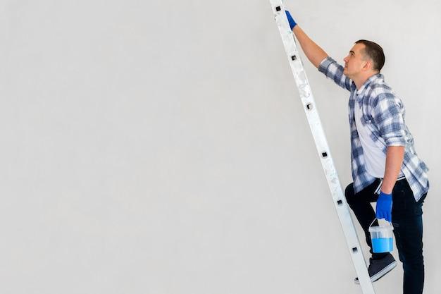 Pracownik chodzenie po schodach, niosąc farbę