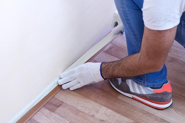 Pracownik chroniący cokoły i podłogi laminowane taśmą maskującą przed malowaniem
