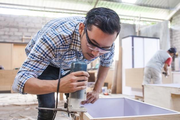 Pracownik cięcia krawędzi deski drewnianej za pomocą piły progowej