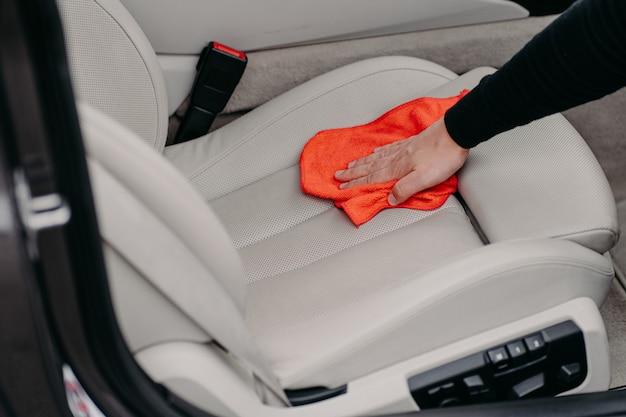 Pracownik czyści fotelik samochodowy