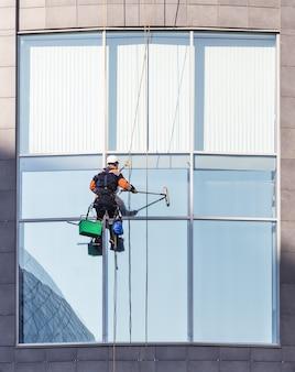 Pracownik czyści okno i biurowy wieżowiec