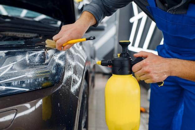 Pracownik czyści powierzchnię samochodu sprayem i szczotką, przygotowując ją przed nałożeniem folii ochronnej. montaż powłoki chroniącej lakier samochodu przed zarysowaniami. pojazd w garażu