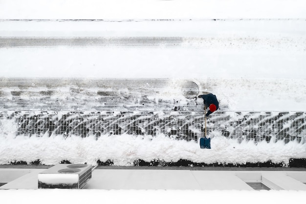 Pracownik czyści śnieg łopatą