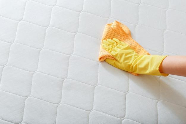 Pracownik czyści szmatką powierzchnię materaca na łóżku. czyszczenie powierzchni dezynfekcyjnych. osoba z firmy sprzątającej ręka w rękawiczce czyszczenie chemiczne materaca. skopiuj miejsce.