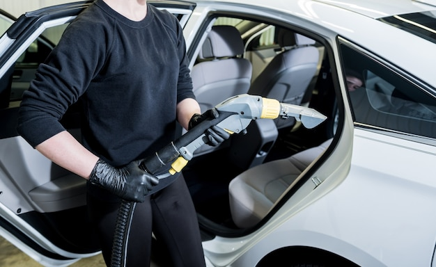 Pracownik czyści wnętrze samochodu za pomocą odkurzacza