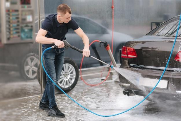 Pracownik czyszczący samochód wodą pod wysokim ciśnieniem.