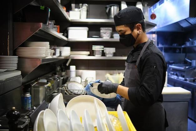 Pracownik czyszczenia naczyń w kuchni restauracji.