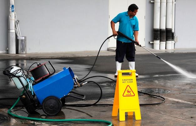 Pracownik czyszczenia podłogi za pomocą maszyny wysokiego ciśnienia powietrza