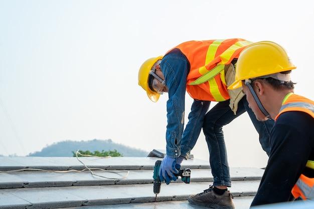 Pracownik dekarz budowniczy dołącza blachę do nowego dachu na górnym dachu, niedokończona konstrukcja dachu.