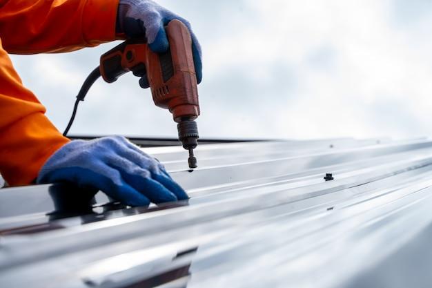 Pracownik dekarz używa pneumatycznego lub pneumatycznego pistoletu do gwoździ i instaluje blachę na nowym dachu.