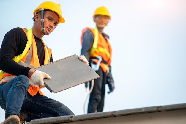 Pracownik dekarza w mundurze ochronnym i rękawiczkach, za pomocą pneumatycznego lub pneumatycznego pistoletu do gwoździ i instalujący betonową dachówkę na nowym dachu, koncepcja budynku mieszkalnego w budowie.