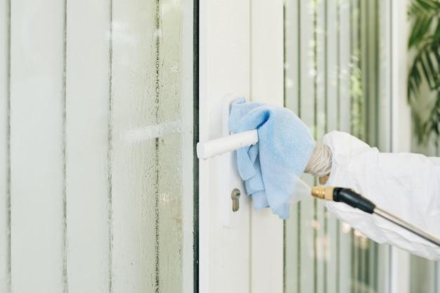 Pracownik dezynfekujący klamkę drzwi