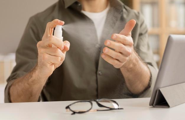 Pracownik dezynfekujący ręce w biurze