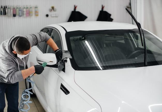 Pracownik dmucha i wyciera samochód po umyciu.