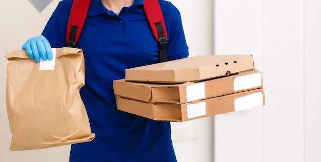 Pracownik dostawy mężczyzna w czerwonej czapce t-shirt t-shirt jednolite rękawice maski dać pudełek po pizzy zamówienia żywności na białym tle na żółtym tle studio. usługa kwarantanny pandemicznej wirusa koronawirusa grypy 2019-ncov koncepcja