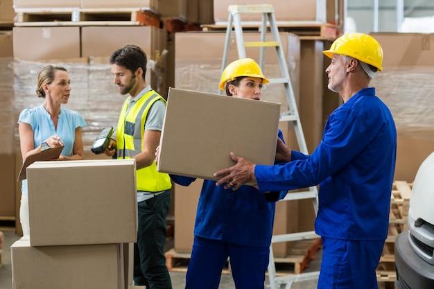 Pracownik dostawy rozładowuje kartony z podnośnika paletowego