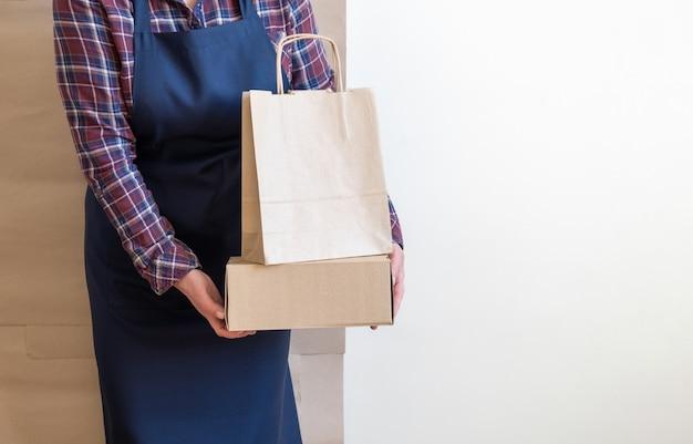 Pracownik dostawy usługa pakuje torby pudełka fartucha pakowacza wysyłka otwiera kawę iść kopiować przestrzeń