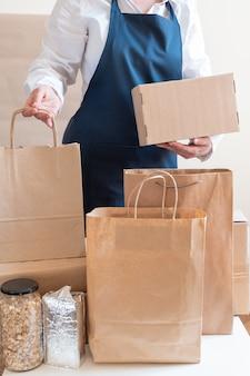 Pracownik dostawy usługi pakowania worek pole fartuch pakowacz ręka post nota wysyłkowa
